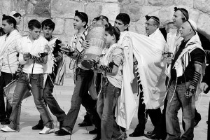 A procession in the Old City of Jerusalem escorting a Bar Mitzvah boy with singing to the Kotel (Western Wall) where he will be called to read from the Torah for the first time. Note that the participants are wearing tefillin which indicates that this is a weekday procession. Casual dress is typical of Israelis even for events such as a Bar Mitzvah.