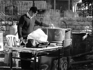 A man stands with large containers of boiling water, ready to kasher (make kosher) untensils for Pesach use. This photo was taken in Meah Sha'arim, a religious area of Jerusalem where apartments are often small and crowded with no storage space available for utensils reserved just for Pesach use.