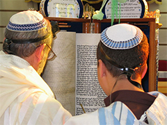 A Sephardi boy reading the Torah at his Bar Mitzvah. The Sephardi custom is for the Torah Scroll to be kept in a wooden case which opens so that it may be read, but the Scroll is not removed from the case. The black straps at the back of the boy's head are part of his tefillin and indicate that this was a weekday Bar Mitzvah since tefillin are not worn on Shabbat.