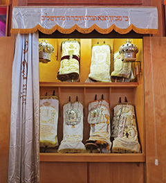 Torah scrolls in an Ashkenazi synagogue Ark (Aron HaKodesh) with the parochet drawn to one side to enable access. The Ark also has solid doors but these are folded back out of the way before the service begins.