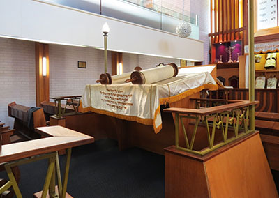 An open Sefer Torah (Torah scroll) lies on the reading desk on the bimah in this synagogue