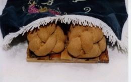 2 loaves of challah partially covered by a challah cloth