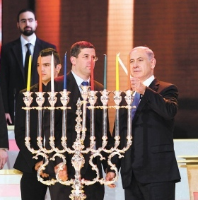 Prime Minister Netanyahu of Israel lighting a chanukiiah on 8th night Chanukah. He uses the shamash light (which, in this chanukiah, will be placed in the central location and higher than the other lights to distinguish it from them) to ignite all the other lights.