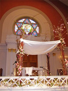 A Jewish marriage ceremony is traditionally carred performed under a chuppah (wedding canopy). Here a chuppah, decorated with blossom, has been erected inside a synagogue and awaits the bridal couple.