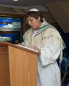 A man leading a prayer service on Yom Kippur and wearing a kittel (white robe) and tallit (prayer shawl). The kittel is worn over the man's ordinary clothes.