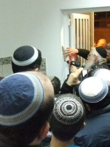 A mezuzah being affixed to the door post during a Chanukat haBayit ceremony