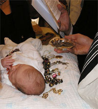 A baby at his Pidyon haBen. Here the ceremony is performed according to Sephardi custom, indicated by the jewellery placed alongside the baby.