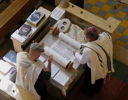 A Torah scroll being read in synagogue. As the text of a Torah scroll is written without vowels, a second man stands adjacent to the reader and checks his reading against a printed edition with vowels, thus enabling him to quickly call out a corretion to any error made by the reader