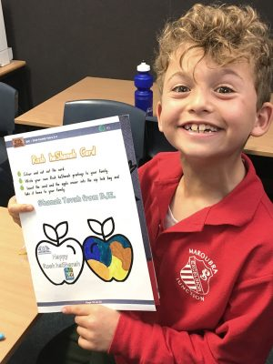 An SRE student showing the Rosh HaShaaaaaaanah greeting card he has made
